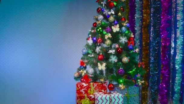 Kék alapon, egy gyönyörűen díszített karácsonyfa ajándékokkal és szilveszteri esővel.