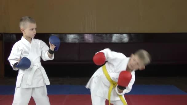 Egy piros overlay-es fiú a kezén rúgást gyakorol egy atléta overlay-jére.