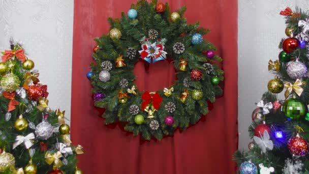 Vánoční věnec váží mezi dvěma zdobenými vánočními stromky