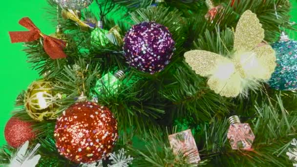 Vánoční stromeček zdobený žárovkami a hračkami se točí na zeleném pozadí