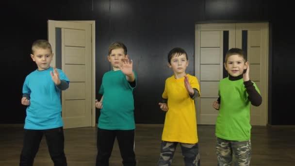 Čtyři sportovci v barevných tričkách trénují punching