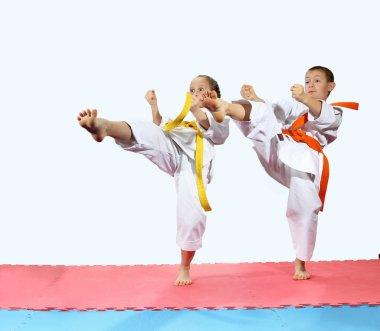 Girl and boy in karategi are beating kick leg forward