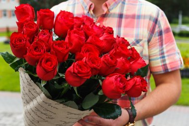 A man carrying a huge bouquet of red roses