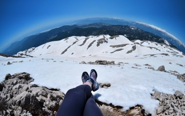 Legs of traveler sitting on a high mountain top in travel,Turkey
