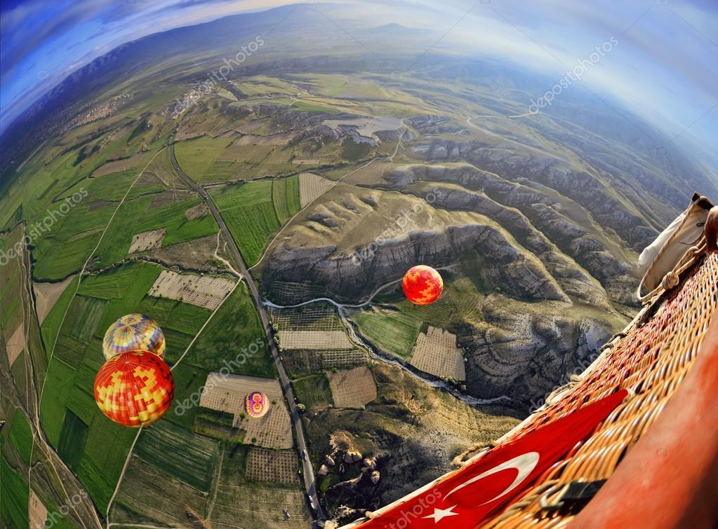 Colorful hot air balloon flying over rock landscape in  blue sky