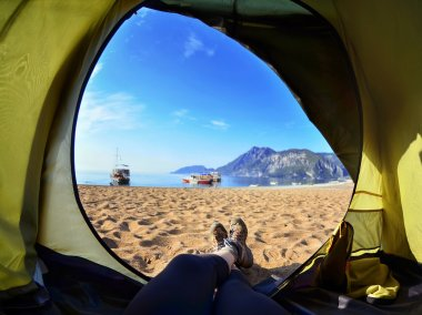 Happy woman sitting in a tent ,view of mountains ,sky and sea.Olympos Beach. Cirali, Turkey