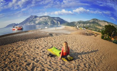 Happy woman lying on the beach ,view of mountains ,sky and sea .