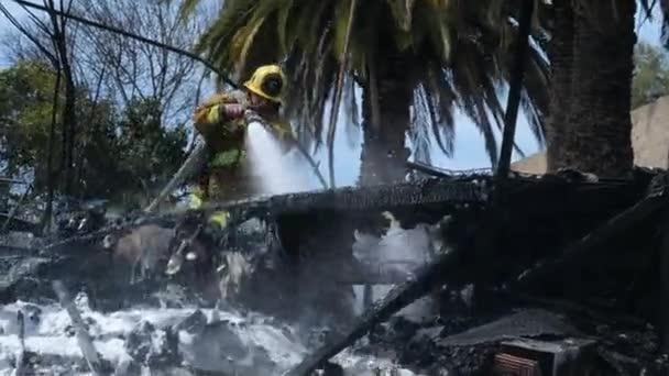 Los Angeles, CA USA - 26. března 2021: Detailní rozstřik vody jako hasič uhasí požár v táboře bezdomovců