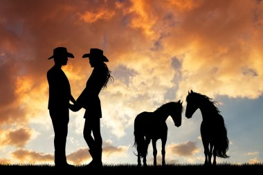 couple of cowboys with horse at sunset