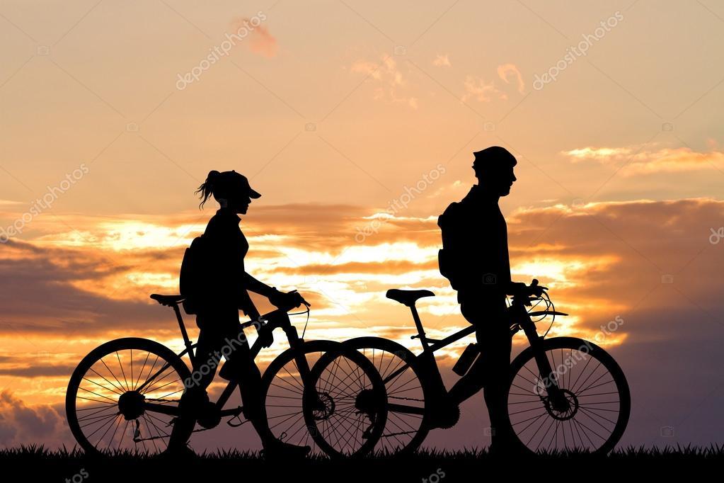 couple with bike at sunset stock photo adrenalina 95343474