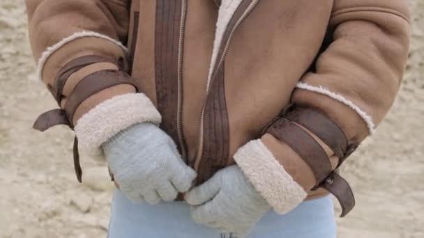 Nahaufnahme eines Mannes, der seine Winterjacke im Freien reißt