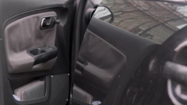 Ein Mann kommt zum Auto, schließt die Tür mit einem Schlüssel