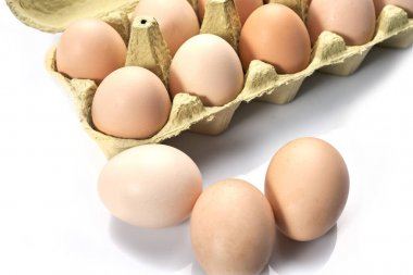 Close-up of eggs in cartoon on white background. Raw chicken eggs in egg box organic food for good health high protein .