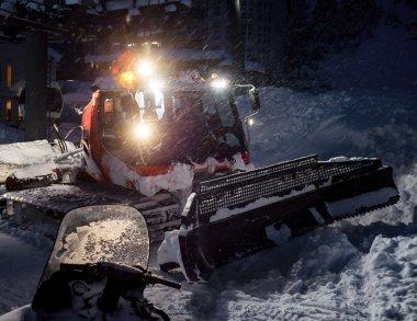 Snowcat preparing a slope in mountains