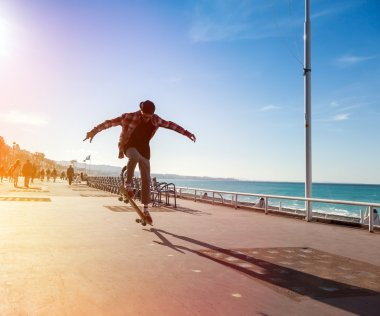 Silhouette of Skateboarder jumping in city on background of promenade and sea stock vector