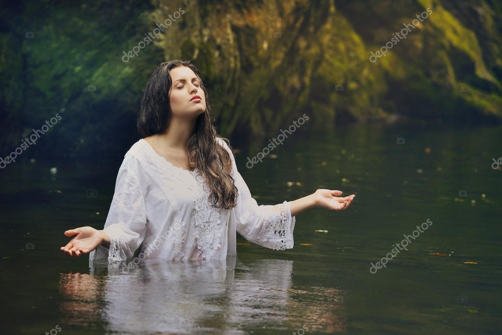 Beautiful woman in colorful forest stream