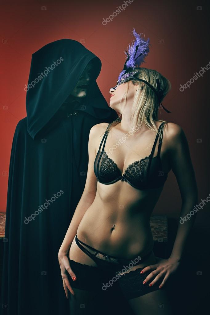 Mysterious masked man and beautiful woman in lingerie