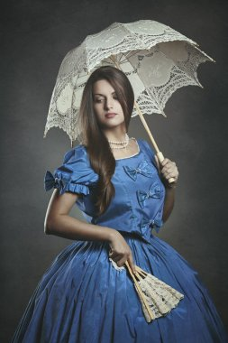 Noble beautiful woman posing with umbrella and fan