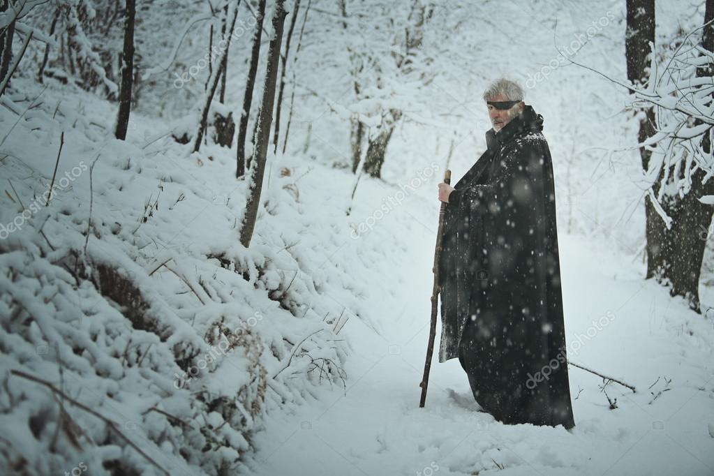 Old one eyed man in a forest with snow