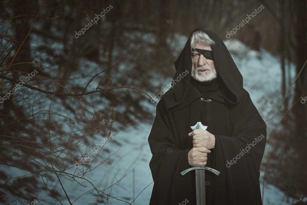 Old one eyed man with sword in dark forest
