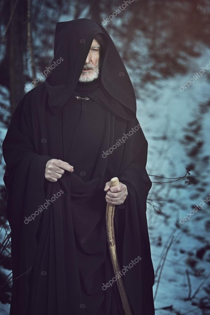 Old white beard pilgrim in dark forest with snow