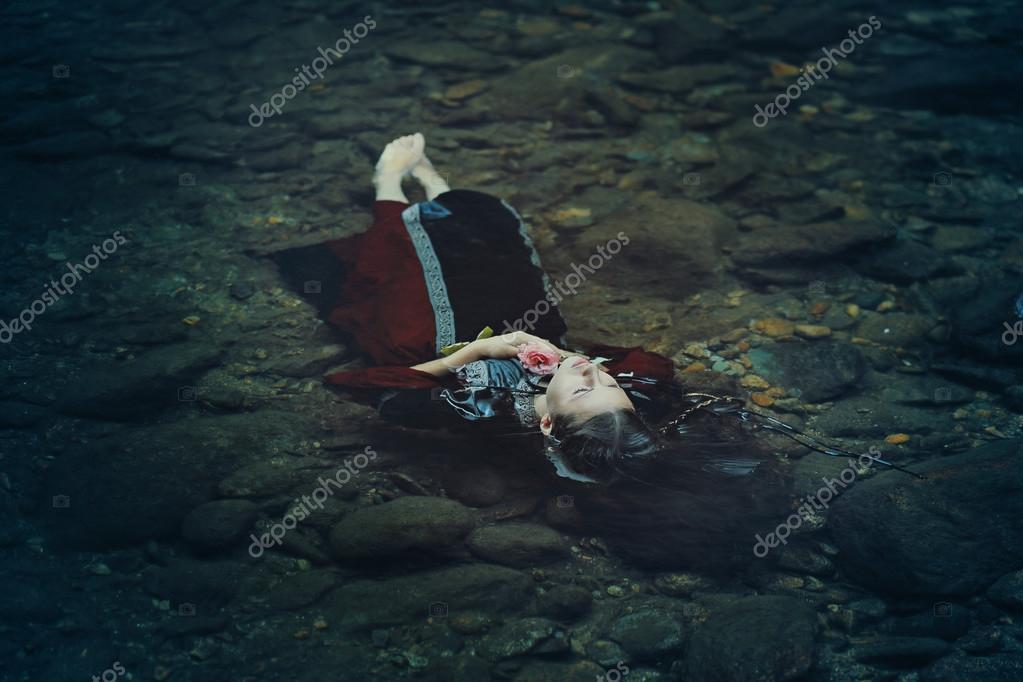 Beautiful floating woman in dark water