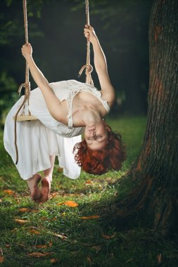 Beautiful woman with eyes closed on a swing
