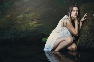 Beautiful woman in forest stream water