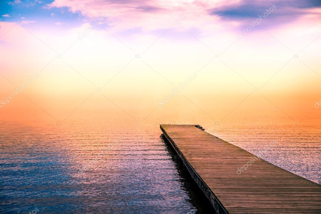 tranquil scene of a pier in the sea with fog