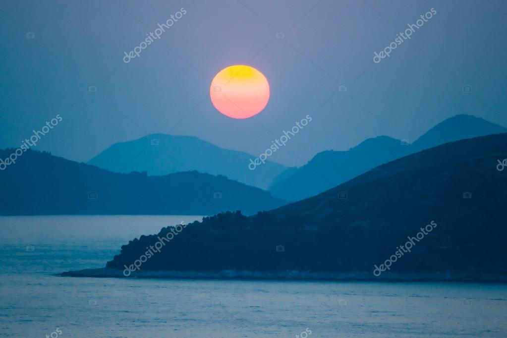 sunset over sea and mountains