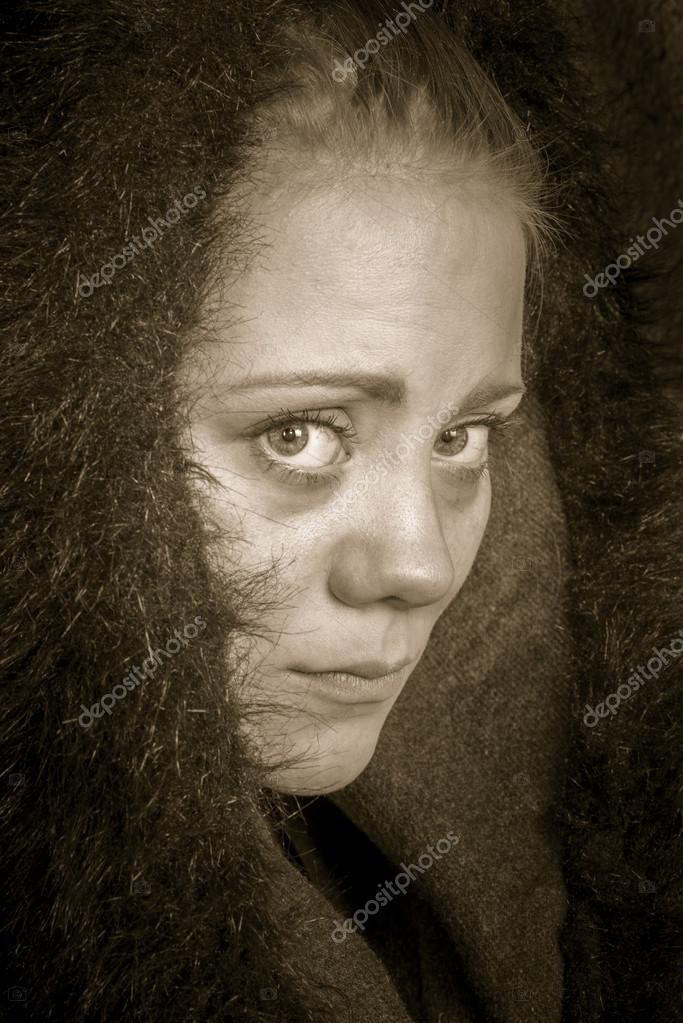 Young female poor beggar in semi profile