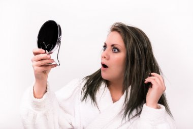 brown haired woman looking shocked at herself in a mirror