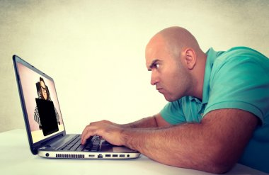 Man looking at angry female with laptop