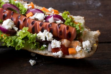 Grilled hot dog with cheese and vegetables