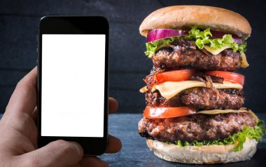 Beef burger and blank screen on the smartphone