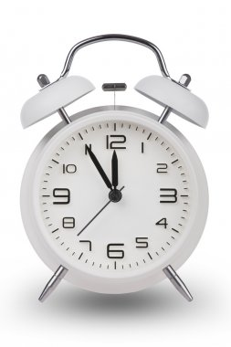 White alarm clock with the hands at 5 minutes till 12. Illustrating Time is Running Out isolated on a white background