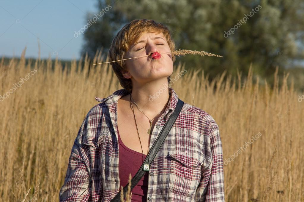 A girl make a funny face on the field with ears in a village