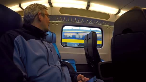 Muž ve vlaku pomocí mobilního telefonu