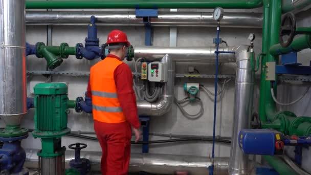 Junger Techniker mit digitalem Tablet zur Datenüberprüfung im Maschinenraum Porträt eines jungen Arbeiters im Fernwärmekraftwerk. Digitales Technologiekonzept. Industrie 4.0