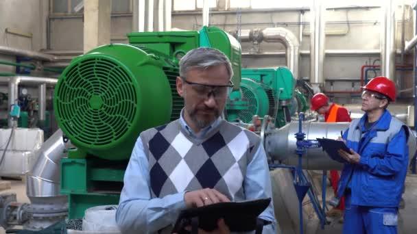 Selbstbewusster Manager mit digitalem Tablet und Daumendrücken im Maschinenraum. Fernwärmekraftwerk. Digitales Technologiekonzept. Teamwork Konzept. Industrie 4.0