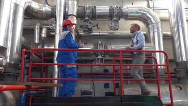 Fernwärmekraftwerk. Factory Engineer mit digitalem Tablet Prüfen der Daten mit dem Technischen Manager. Digitales Technologiekonzept. Industrie 4.0. Ältere Arbeitnehmer in persönlicher Schutzausrüstung.
