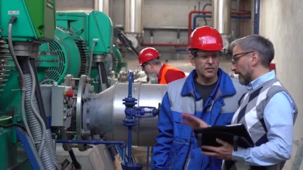 Technischer Leiter mit digitalem Tablet im Gespräch mit Arbeitern in persönlicher Schutzausrüstung. Digitales Technologiekonzept. Industrie 4.0. Fernwärmekraftwerk.