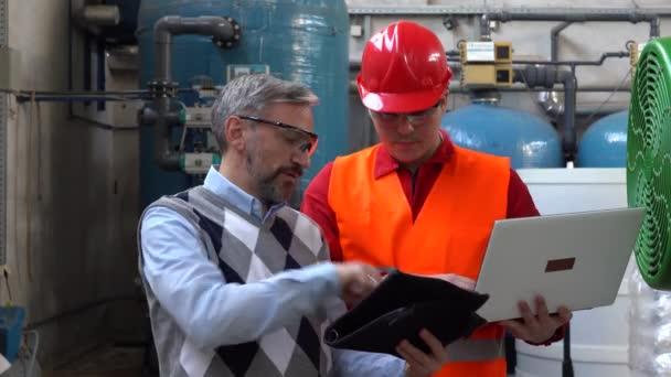Junger Techniker mit Laptop, der Daten mit dem Technischen Leiter im Maschinenraum überprüft. Porträt eines jungen Arbeiters im Fernwärmekraftwerk. Digitales Technologiekonzept. Industrie 4.0 .