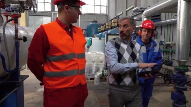 Reifer Manager beaufsichtigt Mitarbeiter im Fernwärmekraftwerk. Manager und zwei Arbeiter eines Bezirkskraftwerks schreiten in Zeitlupe durch den Maschinenraum. Teamwork Konzept. Industrie 4.0