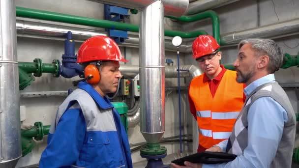 Technischer Leiter mit digitalem Tablet und Diskussion über Produktionsprozesse mit zwei Kraftwerksmitarbeitern in Zeitlupe. Digitales Technologiekonzept. Industrie 4.0