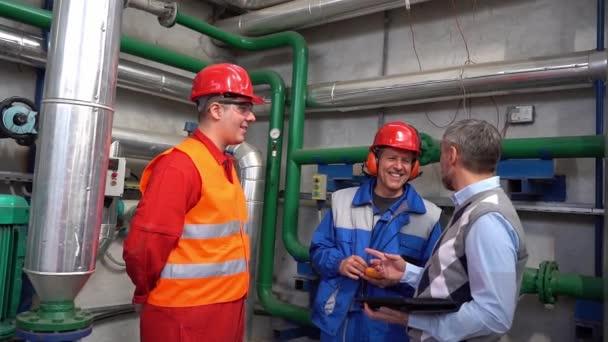 Zwei lächelnde Arbeiter im Gespräch mit dem Leiter des Fernwärmekraftwerks. Zeitlupenvideo. Konzept der Teambildung. Digitales Technologiekonzept. Industrie 4.0