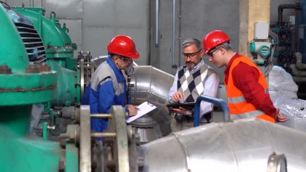 Wartungsingenieur mit digitalem Tablet und diskutiert mit zwei Fabrikarbeitern über den Produktionsprozess. Digitale Technologie und Teamwork-Konzept. Industrie 4.0