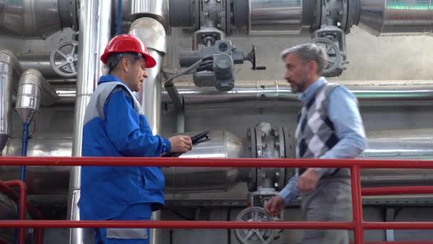 Technischer Leiter und Instandhaltungsingenieur mit digitalem Tablet für die Datenprüfung im Kraftwerk. Digitale Technologie und Teamwork-Konzept. Industrie 4.0