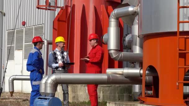 Zwei Ölarbeiter und ein Manager bei einem Treffen vor Tanks der Ölraffinerie. Geschäftsmann mit digitalem Tablet im Gespräch mit zwei Arbeitern in Uniform Digitale Technologie und Teamwork-Konzept.