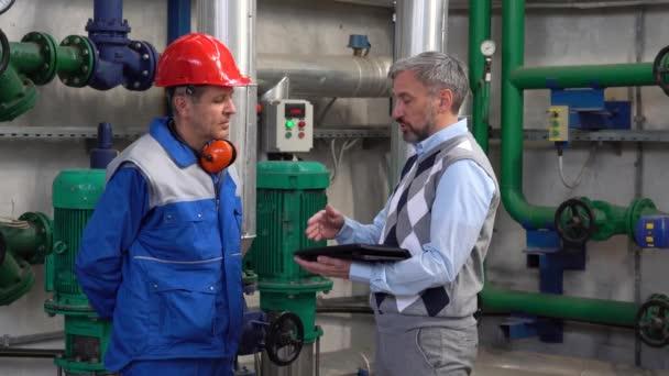 Supervisor mit digitalem Tablet in der Kommunikation mit Industriearbeitern in persönlicher Schutzausrüstung. Fernwärmekraftwerk. Digitale Technologie und Teamwork-Konzept. Industrie 4.0